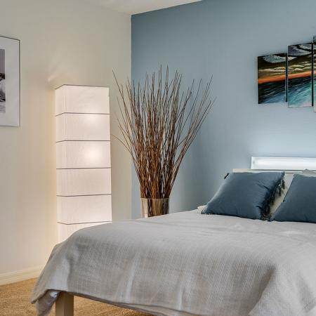 Bedroom with blue accent wall and bed covered with white comforter.  Art hangs on the walls and a decorative plant and lamp flank the left side of the bed.