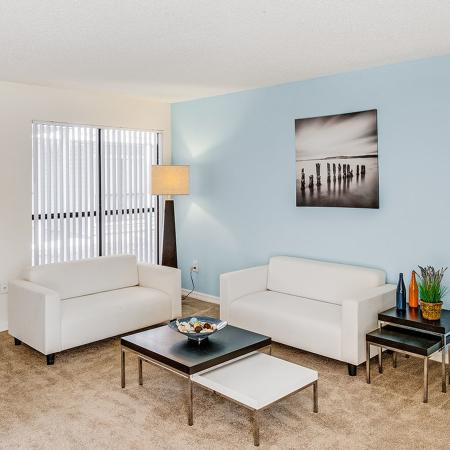 Living area with baby blue accent wall, brown carpet, two white couches, and a dark set of small end tables.