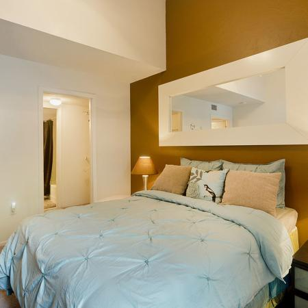 Carpeted bedroom with brown accent wall.  Bed is made up with a light blue bedspread.  Night stands with lamps flank both sides of bed, and a large mirror hangs over headboard.