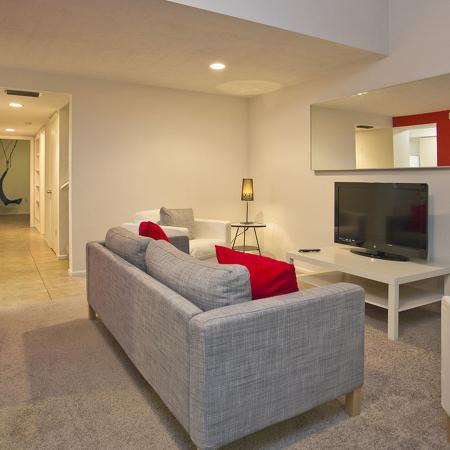 Living area with cloth couch facing flat screen television on a television stand.  Hallway to other areas of the apartment in the background.