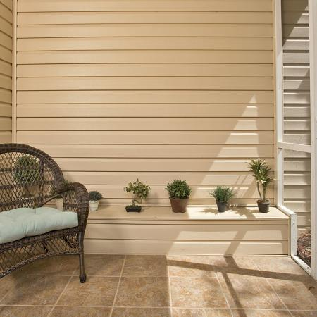 Screened patio with tile floor and wicker chair.  Small plants sitting on top of a built in bench along the wall.