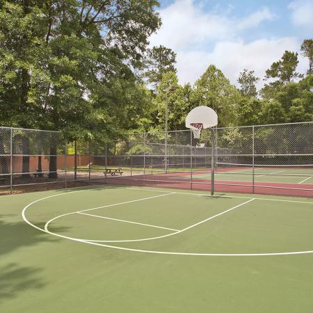 Half basketball court with tennis court and trees in background.