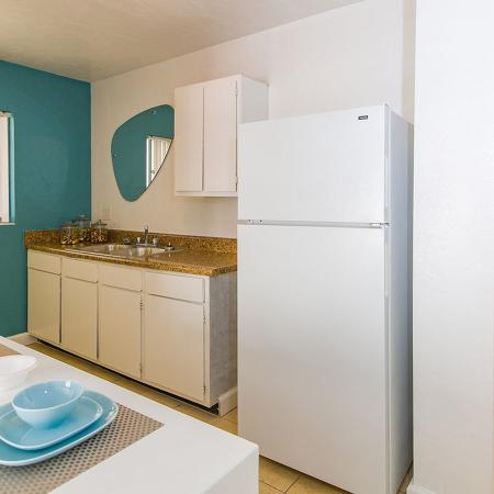 Galley style kitchen with tile floor, white appliances, and pantry with the door open exposing four shelves.