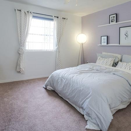 Carpeted bedroom with gray bedspread and lavender accent wall.  Tall dark dresser and tall lamps on both sides of the bed.