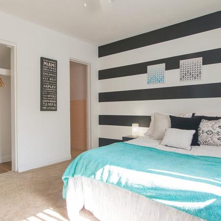 Carpeted bedroom with open closet exposing shelf and coat hangers.  Far wall has a black and white horizontal stripe pattern.