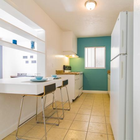 Galley style kitchen with tile floor, white appliances, and a two seat breakfast bar.