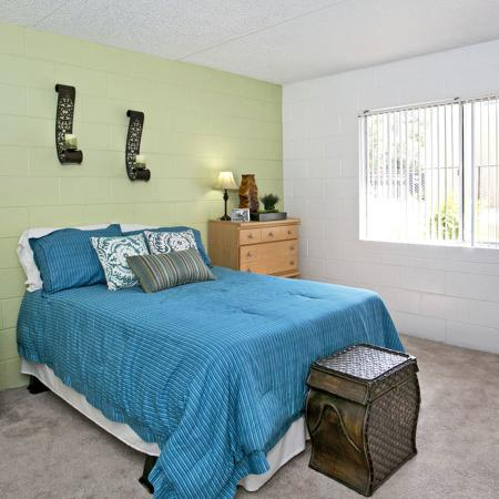 Carpeted bedroom with blue bedspread and light green accent wall.  There is also a wooden dresser and nightstand present.