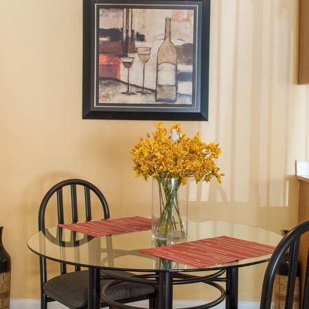 Close up of the glass dining table with two place settings.  Table has a vase with yellow flowers in it, and there is a painting on the back wall.