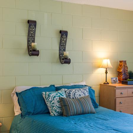 Close up of the bedroom's accent wall showing candle stands mounted on wall.  The photo also shows the wood dresser, nightstand, and two lamps.