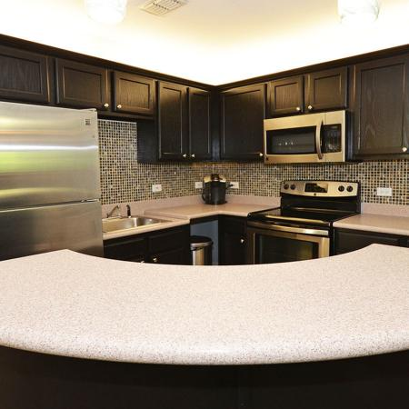 Kitchen with curved breakfast bar, stainless steel appliances, and dark cabinets.