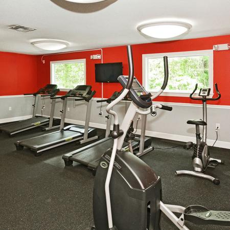 Fitness center with cardio equipment and television.