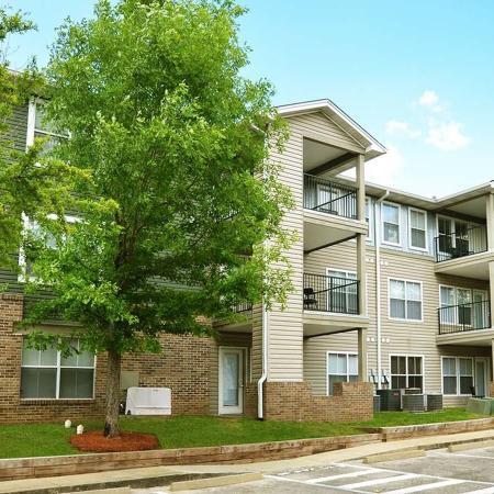 Facade of a three floor apartment buiding, trees.