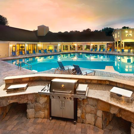 Community pool surrounded by lounge chairs. Gas grill encased in stone counter in foreground.