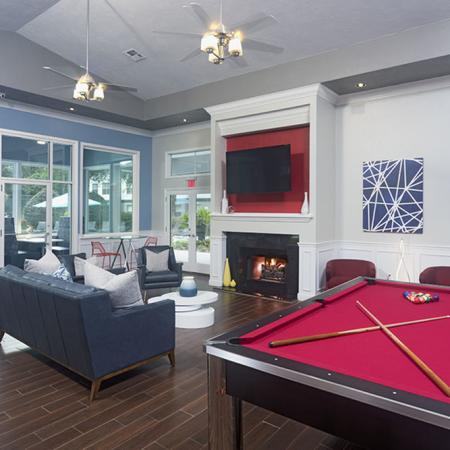 Community clubhouse with couch, tv, fireplace, and pool table.