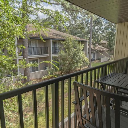 Looking off of balcony with railing, small table and chairs. Trees and building in background.