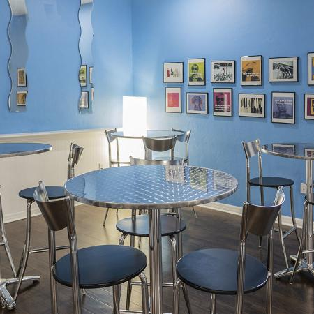Set of four high top tables and chairs on a wood styled floor, and blue walls in background.