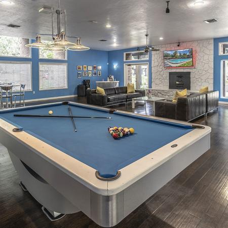 Community clubhouse with pool table, high top table and chairs, television viewing area with leather couches, and wall mounted television.
