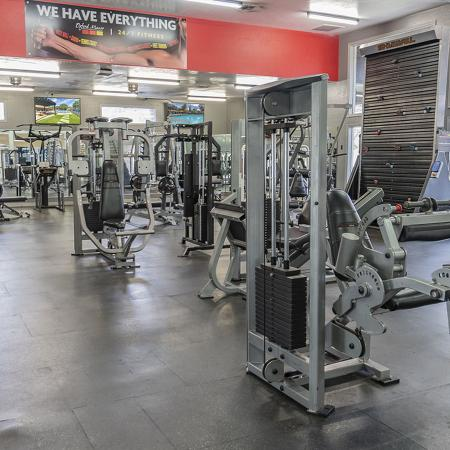 Community fitness center with various weight machines, and wall mounted televisions.