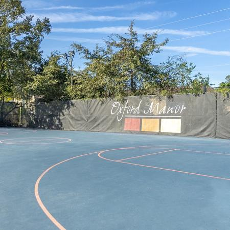 Full size basketball court with fenced in with Oxford Manor logo on hanging banner.