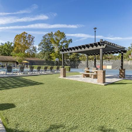 Grassy area inside pavered walkway.  Gazebo and picnic table in the middle.  Pool and tennis court in background.