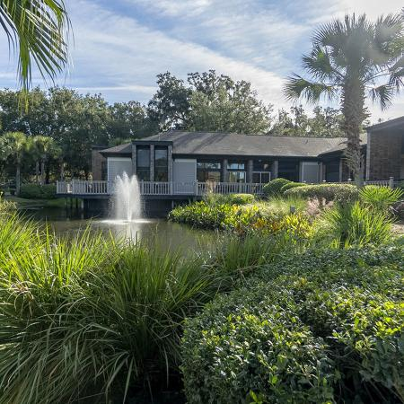 Lush landscaping with pond and fountain, and leasing office in background.
