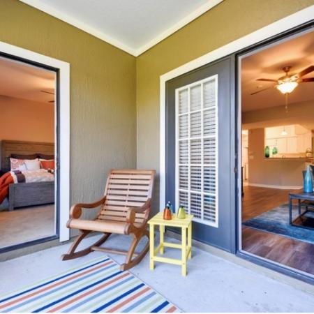 Patio with small wood chair and end table.  Doorways to living room and bedroom are open.