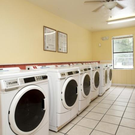 Community laundry facility showing a row of washers on a light tile floor.