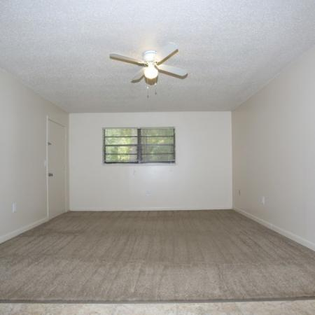 Living area facing the front door and front window.  Area is empty with a beige colored carpet and light color walls.