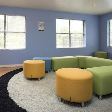 Community social space with green and yellow fabric, sectional seating.