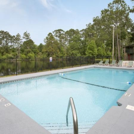 Rectangular community pool with lounge chairs and trees in background.