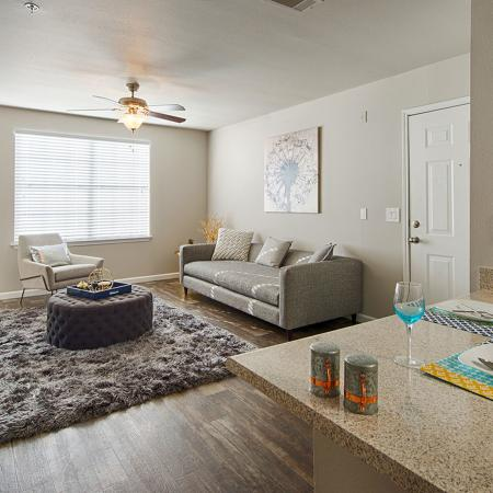 Living area with wood style flooring, couch coffee table, chair, and entertainment center.  Tall table on the right with two place settings.