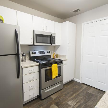 Kitchen with wood style flooring stainless steel appliances, white cabinets with double sink.