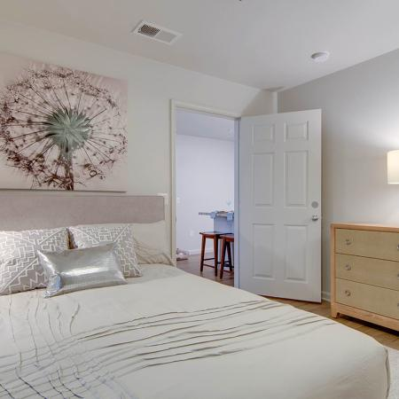 Bedroom with wood style flooring, white comforter with white pillows on bed, dresser and door open to the kitchen area.