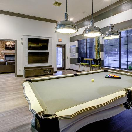 Community game room with billiard table and movie viewing area in background.