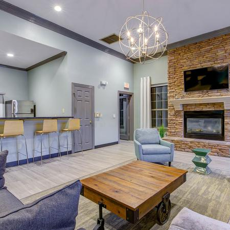 Community social center with a plush couch and several chairs.  Along the side is bar style seating with kitchen appliances behind it.  Background shows a fireplace with a mantel mounted television.