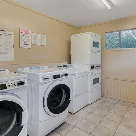 Community laundry facility showing several washers and dryers in a well lighted room..