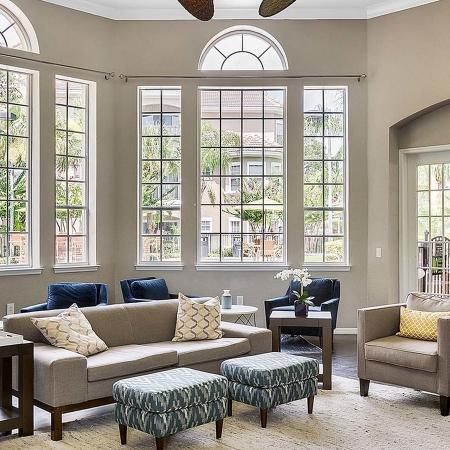 Community clubhouse with tall ceiling and large windows.  Fabric covered couch, chairs,and ottomans.