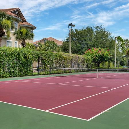 Red and green tennis court surrounded by fence, bushes and trees. Basketball court in background.