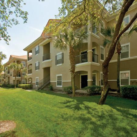 Three floor apartment building with lots of green grass and trees.