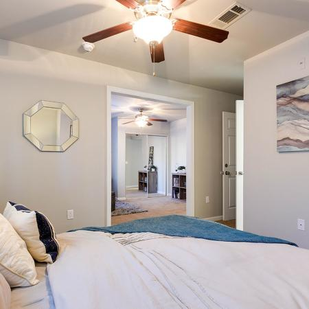 Bedroom with cache colored comforter and pillows. Ceiling fan, mirror and art.