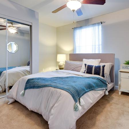 Carpeted bedroom with sliding glass doors on the closet.  Bed has a lavender colored comforter with blue throw blanket.  there is also a nightstand and wicker hamper.