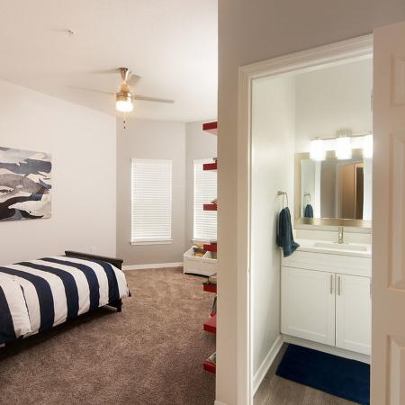 Carpeted bedroom with made bed.  Open door to bathroom exposing the vanity on the right.