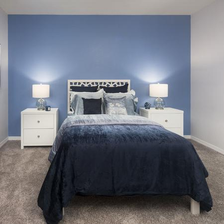 Carpeted bedroom with blue comforter on bed, blue accent wall, white nightstands and dresser.  Nightstands have lamps on them.  Open doorway to bathroom on right side.