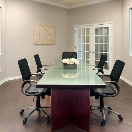 Community meeting room with wood style flooring, long table with five chairs.