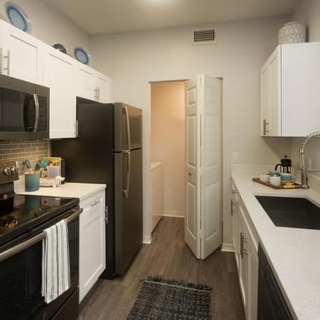 Galley style kitchen with white cabinets, black appliances, under-mount sink, and pantry door open in the background.