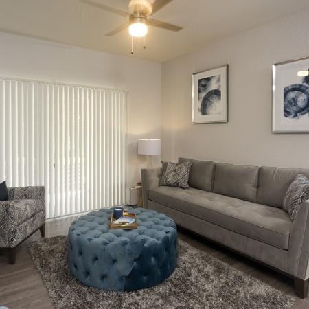 Living room with wood style flooring, soft fabric couch, ottoman, chair, and double doors with vertical blinds that are closed.