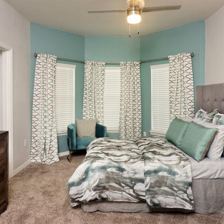 Carpeted bedroom with fluffy comforter and pillows on bed. Bay window on far side with wall painted green.