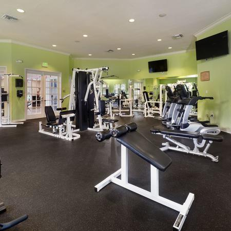 Community fitness center with various cardio and weight machines.  Two wall mounted televisions.