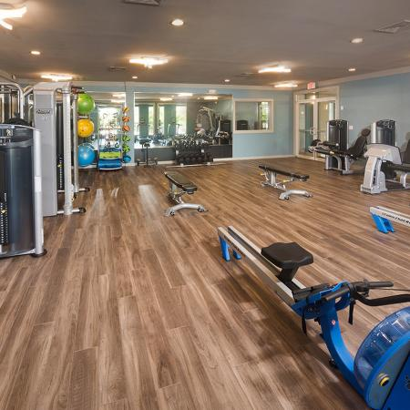 Gym with wood floor, mirrors, cardio machine in forefront.