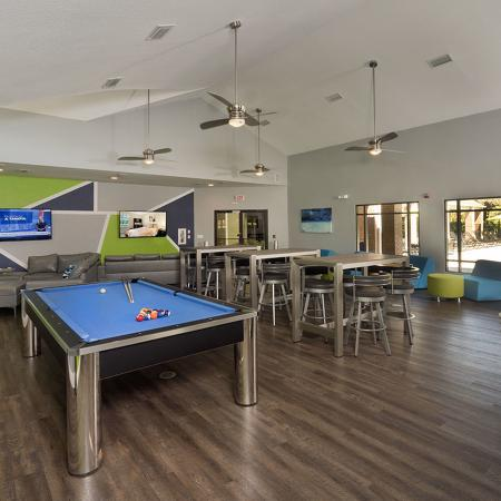 Community clubhouse with pool table, hightop table and chairs in foreground, television viewing area in background.